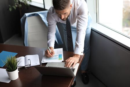 Elegant modern businessman analyzing data while working in office