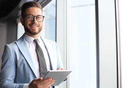 Modern business man in formalwear using digital tablet while standing near window in the office Banque d'images - 130734222