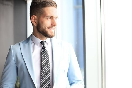 Modern business man in formalwear standing near window in the office Banque d'images - 130734246