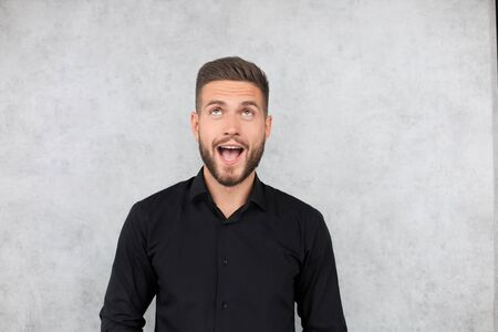 Surprised young man is looking at camera with open mouth isolated over gray background Banque d'images - 130734432