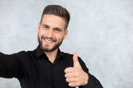 Photo of cheerful handsome young man standing isolated over grey background showing thumbs up Banque d'images - 130734443