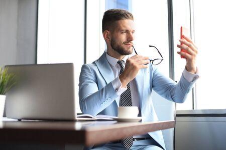 Modern smiling businessman is taking a selfie in the office Фото со стока