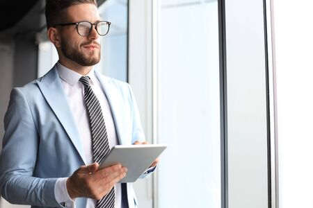 Modern business man in formalwear using digital tablet while standing near window in the office Banque d'images - 130734482