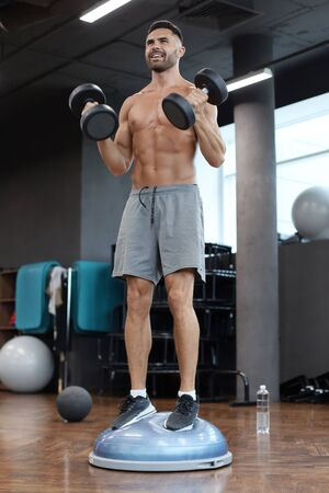 Fit and muscular man working out with bumbbells on gymnastic hemisphere bosu ball in gym.