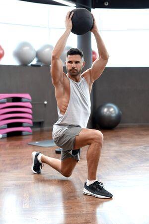 Hombre en forma y musculoso ejercicio con balón medicinal en el gimnasio.