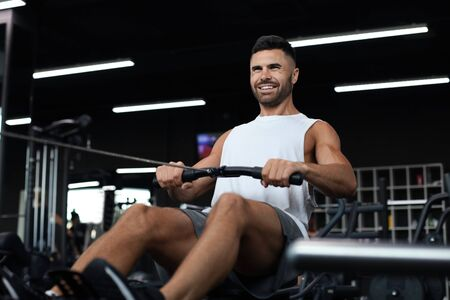 Fit and muscular man using rowing machine at gym.