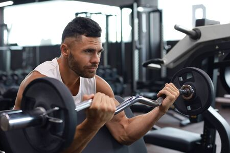Fit and muscular man lifting heavy barbell weight using bench at the gym.
