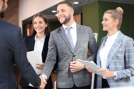 Zakelijke partners handenschudden over zakelijke objecten op de werkplek. Stockfoto