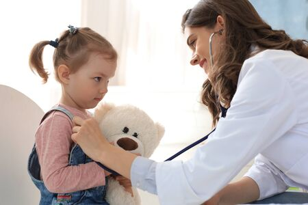 Little girl at the doctor for a checkup. Doctor woman auscultate the heartbeat of the child