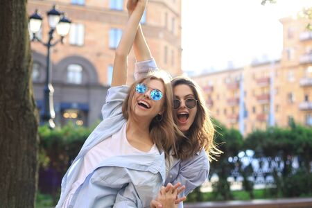 Two beautiful smiling girls in trendy summer clothes posing on street background. Models are having fun and hugging Stok Fotoğraf