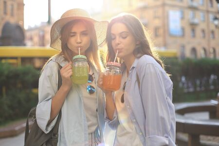 Two young beautiful smiling woman in summer clothes are having fun in city and drinking fresh cocktail