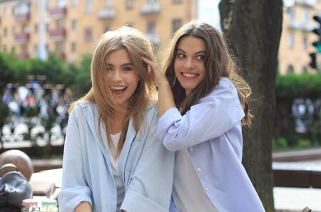Two young smiling hipster women in summer clothes posing on street.Female showing positive face emotions