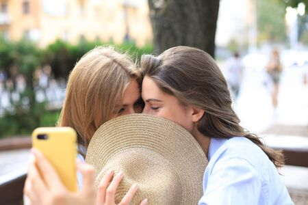 Two women friends are hiding kissing each other while selfie for fun Stock Photo