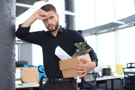 Sad dismissed worker is taking his office supplies with him from office. Stock Photo