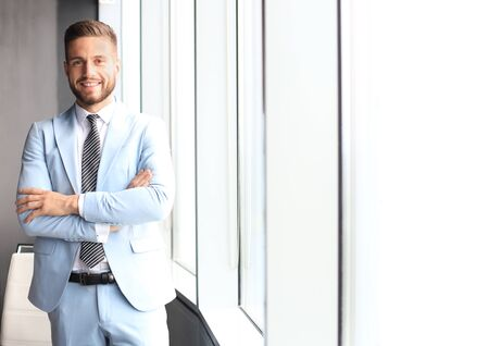 Portrait of happy businessman with arms crossed standing in office. Imagens