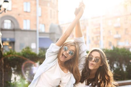 Two beautiful smiling girls in trendy summer clothes posing on street background. Models are having fun and hugging Stock fotó