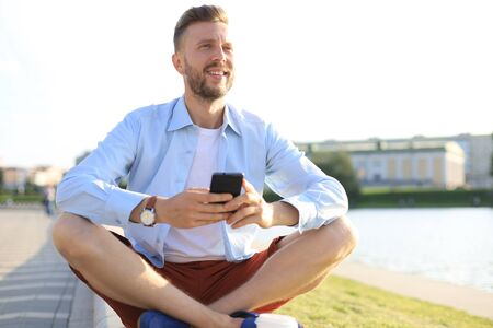 Happy young handsome man sitting on the bench outdoors and using smartphone.