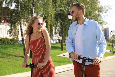 Lovely couple having fun driving electric scooter through the city. Stock fotó