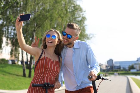 Lovely couple having fun driving electric scooter through the city, having a break, taking selfie. Stock Photo