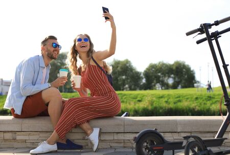 Lovely couple having fun driving electric scooter through the city, having a break, taking selfie.