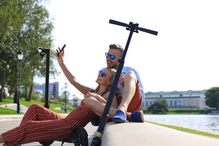 Lovely couple having fun driving electric scooter, taking a break from driving, sitting on riverbank, taking selfie, Stock fotó