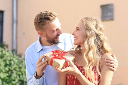 Astonished excited couple in summer clothes smiling and holding present box together while standing on city street.