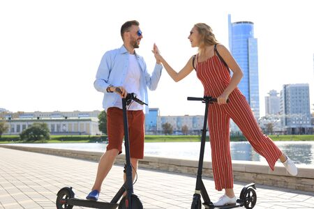 Lovely couple having fun driving electric scooter along the city promenade.
