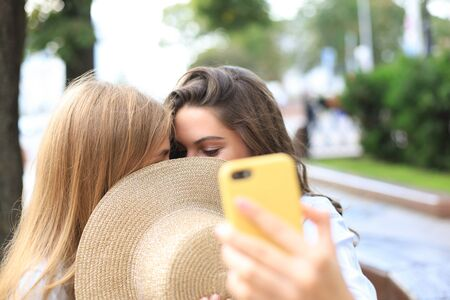 Two women friends are kissing each other for fun Stock fotó