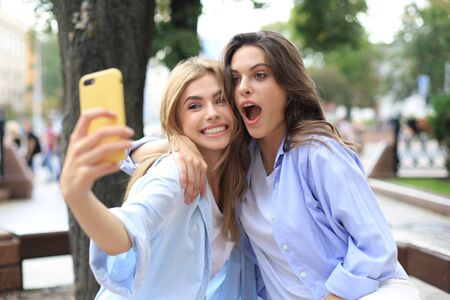 Two laughing friends enjoying weekend together and making selfie on city background Stock fotó