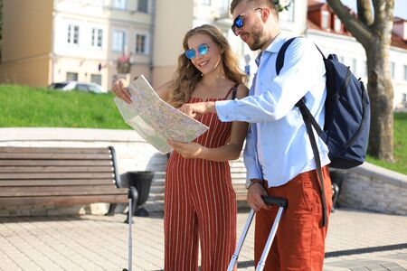 Lovely couple on vacation are looking at map for direction.