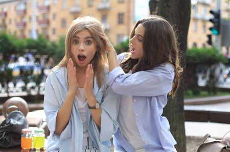 Two young smiling hipster women in summer clothes posing on street.Female showing positive face emotions. Stock fotó