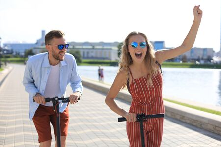 Lovely couple having fun driving electric scooter along the city promenade