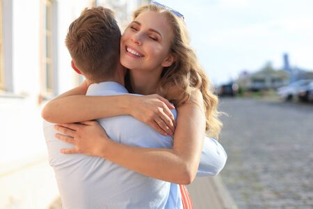 Beautiful young couple in love walking outdoors at the city street, hugging Stock fotó