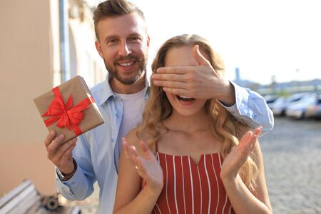 Portrait of a happy young couple hugging while standing together with a present box, man covers eyes of woman