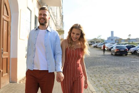Beautiful young couple holding hands and smiling while walking through the city street