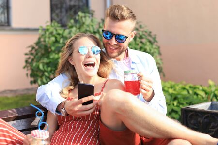 Romantic young couple in summer clothes smiling and taking selfie while sitting on bench in city street