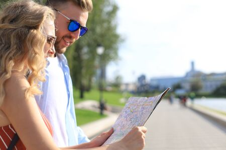 Lovely couple on vacation are looking at map for direction Stock fotó