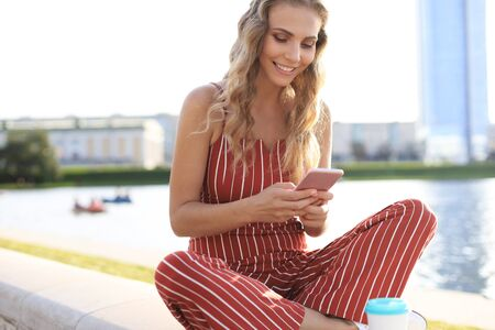 Portrait of pretty young woman sitting on riverbank with legs crossed during summer day, using smartphone