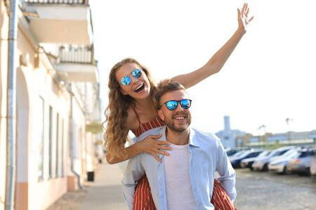 Handsome young man carrying young attractive woman on shoulders while spending time together outdoors Stock fotó