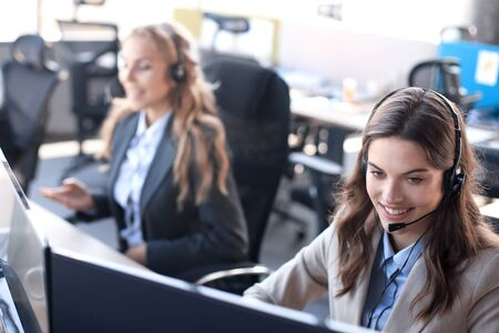 Female customer support operator with headset and smiling, with collegues at background Stock fotó
