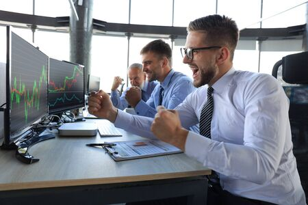 Group of modern business men in formalwear analyzing stock market data while working in the office Banque d'images - 131933478