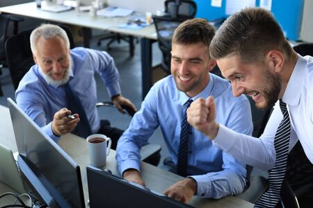 Group of modern business men in formalwear smiling and gesturing while working in the office Stock fotó