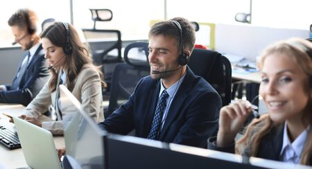 Portrait of call center worker accompanied by his team. Smiling customer support operator at work