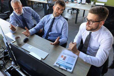 Group of young business men in formalwear working using computers while sitting in the office