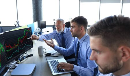 Group of modern business men in formalwear analyzing stock market data while working in the office