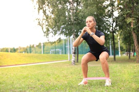Sporty woman doing squats with fitness gum expander in the park outdoors