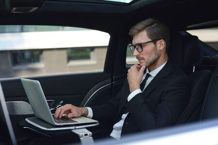 Thoughtful young businessman keeping hand on chin while sitting in the lux car and using his laptop