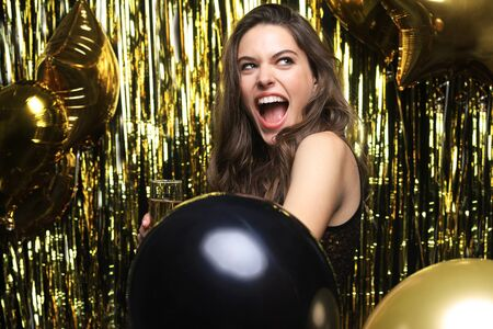 Cheerful woman with balloons laughing on gold background