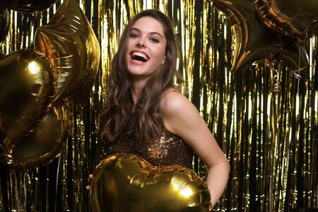 Happy woman in festive outfit holding gold balloons