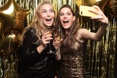 Beautiful girlfriends in high spirits take selfie at party on gold background